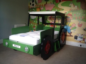 dark green tractor with red wheels in front of farm mural